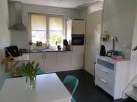De open keuken met moderne, lichte inrichting is voorzien van een koelkast, vaatwasser, combi-oven, afzuigkap en gaskookplaat. Vanuit de keuken heeft u mooi uitzicht naar buiten.
