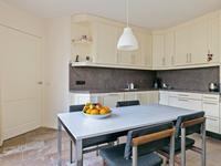 Vanuit de woonkamer komt u in de woonkeuken. Deze is voorzien van een nette maatwerk keukeninrichting in hoekopstelling uitgevoerd met een granieten aanrechtblad met 1,5 spoelbak en Miele inbouwapparatuur, namelijk een koelkast, vriezer, afzuigkap, inductiekookplaat en vaatwasser. <BR>De betegelde verdiepte kelderkast is heerlijk als provisieruimte. <BR><BR>Vanuit de keuken heeft u middels dubbele tuindeuren toegang tot het aangrenzende overdekte terras met de avondzon. Hier is ook een gasaansluitpunt voor terrasverwarming aanwezig.