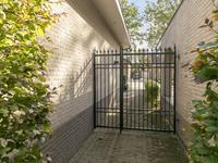 Buiten de woning:<BR>Bestrate oprit met toegang tot de garage. <BR>Zeer fraai aangelegde, onderhoudsvriendelijke voor- en achtertuin met een mooi natuurstenen zonneterras, volop groen en veel privacy.  Gezellig overdekt terras met elektrisch zonnescherm en natuurstenen vloer, aangrenzend aan de leefkeuken.