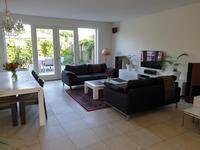 De royale woonkamer is voorzien van een lichte tegelvloer, een provisieruimte onder de trap (met de opstelling vloerverwarmingsunit) en via de openslaande tuindeuren is de achtertuin bereikbaar.