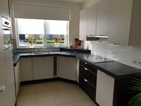 De open keuken met moderne, U-vormige keukenopstelling is voorzien van diverse kastjes, een werkblad met 1,5 spoelbak en naast een inductiekookplaat en afzuigkap zijn ook een vaatwasser, combi-magnetron en koelkast ingebouwd.