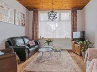 Nette woonkamer met een warme eiken houten vloer, schuifdeuren tussen de voor- en achterkamer en een houten schroten plafond. In beide kamers is de schouw nog aanwezig.