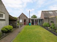 De tuin is aangelegd met een terras met zonnescherm, gras en bloemenborders.<BR>Achterin staat de vrijstaande, stenen garage welke in spouw in 2000 is gebouwd. De garage heeft een stalen kanteldeur welke vanaf de achterzijde is te benaderen.