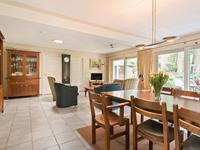 Royale woonkamer met dezelfde lichte tegelvloer, solartube en stucwerk wanden en plafond.