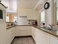 Semi open keuken met tegelvloer en keukeninrichting in U-opstelling voorzien van een dubbele spoelbak, inductie kookplaat, afzuigkap, magnetron, koelkast en vaatwasser.