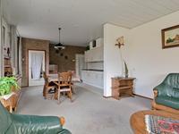 Vanuit de hal komt u in de woonkamer met open keuken.<BR>De kamer is voorzien van vloerbedekking, volop lichtinval door de grote raampartijen en de uitbouw aan de voorzijde. Het plafond is voorzien van MDF panelen.