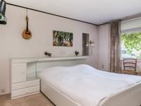 De hal biedt tevens toegang tot de woonkamer en een slaapkamer met aangrenzende badkamer.