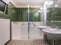Deze badkamer is deels betegeld en voorzien van een royale inloopdouche en twee wastafels.