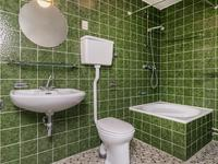 Geheel betegelde badkamer met douche, closet, wastafel en aansluiting voor wasapparatuur.