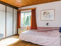 Slaapkamer met wastafel en kastenwand.