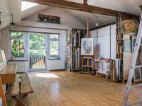 Grote ruimte (atelier) met inbouwkasten, vliering en balkontoegang.