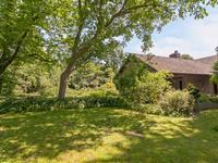 Weelderige tuin rondom met diverse terrassen, beplanting, bessenstruiken, vijverpartij en achterom.