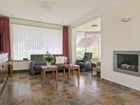 Royale doorzon woonkamer met een leisteen vloer, schuurwerk plafond en aan de achterzijde een schuifpui met toegang tot de achtertuin. Bij de sfeervolle gashaard is de zithoek gerealiseerd van waaruit u heerlijk wegkijkt.