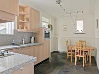 Aparte woonkeuken met diezelfde leisteen vloer en een nette keukeninrichting welke is voorzien van een granieten aanrechtblad, koelkast, kookplaat en vaatwasser.