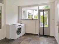 Praktische bijkeuken met 2 inbouwkasten en deuren naar de tuin, de carport en de inpandige garage.