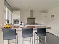 Prachtige open keuken met een tegelvloer met vloerverwarming en een fraaie keuken inrichting met een schiereiland werkblad. De keuken is voorzien van inbouwapparatuur zoals; koelkast, gaskookplaat, afzuigkap, combi magnetron en vaatwasser.