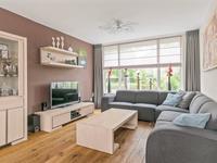 Sfeervolle L-vormige woonkamer met houten vloer, schuurwerk wanden en praktische inbouwkast.