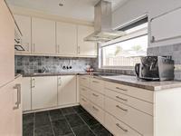In de aanbouw (1994) gesitueerde woonkeuken met tegelvloer voorzien van vloerverwarming en moderne hoek keukeninrichting voorzien van een granieten aanrecht, vaatwasser, combi oven, inductie kookplaat, afzuigkap en koel- vries combinatie.