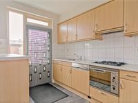 Dichte keuken met tegelvloer, deels betegelde wanden en schuurwerk plafond. De mdf keukeninrichting is voorzien van een gaskookplaat, afzuigkap, combi magnetron, vaatwasser en koelkast met vriezer.
