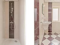 Geheel betegelde badkamer voorzien van een wastafel en douche.