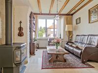 L-vormige woonkamer met een schouw, marmeren vloer in een lichte kleurstelling voorzien van vloerverwarming, geschilderde metselwerk wanden en een balken plafond.
