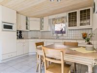 In de aanbouw gesitueerde riante woonkeuken met een tegelvloer. De keukeninrichting is in een hoekopstelling geplaatst en voorzien van een gaskookplaat, afzuigkap, combi-magnetron, koelkast en vaatwasser.