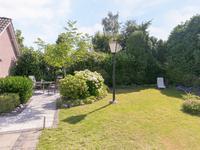 Aangelegde privacy biedende achtertuin met gazon, volop groen, sierbestrating en achterom.