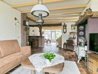De gezellige woonkamer is royaal van opzet en heeft meerdere zithoeken en een bar. Aan de voorzijde is een schouw met mooie houtkachel en uitermate charmant zijn de oude balken die nog in het zicht zijn gebleven.