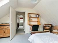Een slaapkamer aan de voorzijde is uitgevoerd met een dakvenster en de andere slaapkamer aan de voorzijde beschikt over een wastafel.