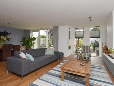 Riante sfeervolle woonkamer met veel lichtinval en schuifpui naar de tuin.