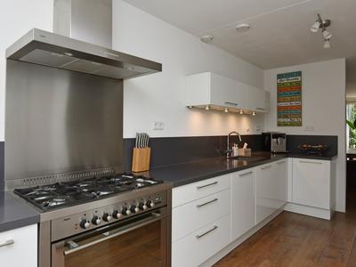 Luxe keuken aan voorzijde met inbouwapparatuur.