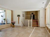 Begane grond; <BR><BR>Via imposante en met natuursteen afgewerkte trappartij naar ruime en lichte ontvangsthal van ca. 22 m2 met natuurstenen tegelvloer, voorzien van vloerverwarming, stucwerk wanden en stucwerk plafond met inbouwspots, tuindeur naar buitenterras met elektrisch bedienbaar brede zonneluifel, geheel betegeld toilet met wandcloset en fontein;