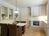 Dichte woon/leef- keuken van ca. 17 m2 met natuurstenen tegelvloer, voorzien van vloerverwarming, en een lichte Poggenpohl keukeninrichting in hoekopstelling voorzien van keramische kookplaat, afzuigkap, combi-oven/magnetron, vaatwasser, koel/vries combinatie, Corian werkblad en mooi uitzicht over de voortuin en het bosrijke straatbeeld;
