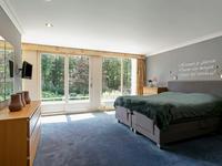 Slaapkamer 1 van ca.38 m2 met schuifpui naar balkon aan de achterzijde en prachtig uitzicht over de achtertuin, t.v. aansluiting, toegang naar eigen geheel betegelde badkamer, voorzien van douchecabine, duo-ligbad, wandcloset, bidet, 2 wastafels met badkamermeubel en een ruime inloopdressing met vaste kasten en spiegelwand;