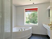 2e geheel betegelde badkamer met ligbad, douchecabine en 2 wastafels;