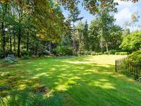 De tuin is grotendeels geheel omheind en heeft een extra ontsluiting via een dubbele poort naar het achtergelegen bos. Daarnaast is de tuin, middels een grondwaterpomp, voorzien van een beregeningsinstallatie en er bevinden zich in de tuin vele volwassen bomen, veel blijvend groen met o.a. vele rododendrons, een royaal gazon en een tuinberging met houtopslag voor de open haard. Kortom, een oase van rust en zie de prachtige foto's verder in de brochure!