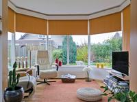 """Aangrenzend aan de woonkamer is de serre / tuinkamer aangebouwd, deze is volledig voorzien van ramen waardoor u hier gevoelsmatig """"in"""" uw tuin zit."""