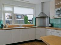 Aparte gesloten keuken met houten vloer en keukeninrichting in een hoekopstelling voorzien van een dubbele spoelbak, inductiekookplaat, oven, koelkast en magnetron.