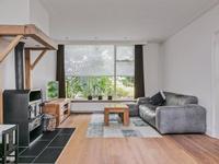 De ruime doorzon woonkamer heeft ook schuurwerk wanden en plafonds en ook dezelfde prachtige houten vloer. Er is een houtkachel aanwezig waar een stenen vloer onder ligt.