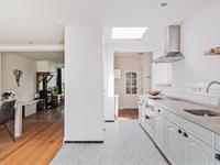 De open keuken heeft een moderne terrazzovloer en een lichtstraat voor extra lichtinval. De keuken, in een wandopstelling, is voorzien van een granieten aanrechtblad en diverse inbouwapparatuur zoals een oven, inductiekookplaat, afzuigkap, vaatwasser en koelkast.<BR>Tussen de keuken en hal zit nog een ruimte waar zich de c.v. kast bevindt met de c.v. ketel uit 2010.