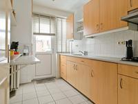 Dichte keuken met tegelvloer en nette keukeninrichting in een wandopstelling voorzien van gaskookplaat, afzuigkap, koelkast en spoelbak. Aan de andere zijde is een makkelijk (wegklapbaar) werkblad.