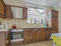 De semi-open keuken heeft een inrichting in een hoekopstelling met diverse kastjes, een aanrechtblad met dubbele spoelbak, een keramische kookplaat met afzuigkap, een koelkast en een oven. Hier is een mogelijkheid voor het plaatsen van een eettafel.<BR><BR>Aangrenzend aan de keuken is er een praktisch portaal c.q. bijkeuken voor de wasapparatuur. Via de achterdeur is de tuin bereikbaar.
