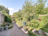 De achtertuin is op het Zuidwesten gelegen en biedt u een fraai aangelegde tuin met borders en een vijver om van te genieten. Er is een overdekte achterom aan de zijkant met een poort. Achterin de tuin staat een prieel (ter overname). <BR>Direct aan het huis is een overkapping geplaatst met inbouwverlichting van waaruit u de avondzon ziet ondergaan.