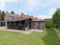 Vrijstaande houten garage / berging met openslaande deuren.