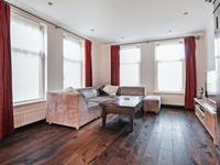 De L vormige breed opgezette woonkamer is voorzien van diezelfde warme houten vloer, heeft schuurwerk wanden en plafond en geeft middels de schuifpui toegang tot de tuin.