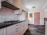 De semi-open keuken, ligt aan de voorzijde, en is voorzien van een leistenen vloer. De keukeninrichting, in een U-opstelling, heeft een granieten aanrechtblad, gaskookplaat, afzuigkap, vaatwasser en combi magnetron.