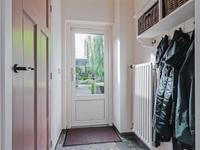 Portaal vanuit de keuken met de inbouwkast waarin de aansluiting voor de wasmachine is.