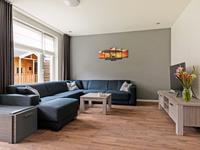 L-vormige woonkamer met laminaatvloer en schuurwerk wanden en plafond.