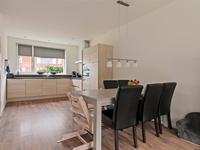 Open keuken met een laminaatvloer, schuurwerk wanden en spuitwerk plafond.