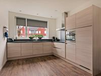 De keukeninrichting is in hoekopstelling geplaatst en voorzien van inductiekookplaaat, afzuigkap, koelkast, vaatwasser en combi-oven.